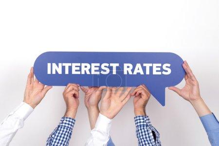 Photo pour Groupe de personnes détenant le taux d'intérêt écrit bulle - image libre de droit