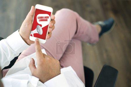 Foto de Personas con teléfono inteligente y el concepto de anuncio de aprender un nuevo idioma en pantalla - Imagen libre de derechos