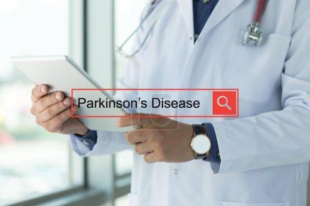 Photo pour Médecin à l'aide de la tablette, la recherche de texte, la maladie de Parkinson - image libre de droit