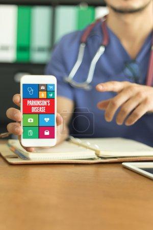 Photo pour Jeune et professionnelle médecin montrant un smartphone. Concept de la maladie de Parkinson à l'écran - image libre de droit
