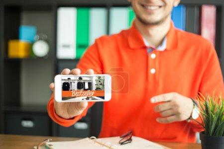 Photo pour Homme tenant dans la main, les smartphone Best-seller Concept - image libre de droit