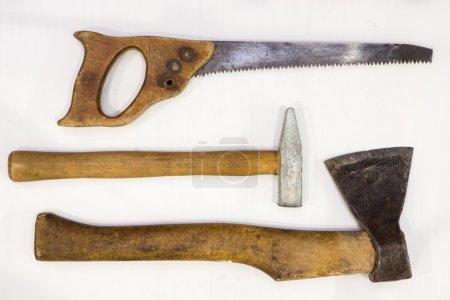 carpenter tools: an ax, a hammer, a hand saw on a light background