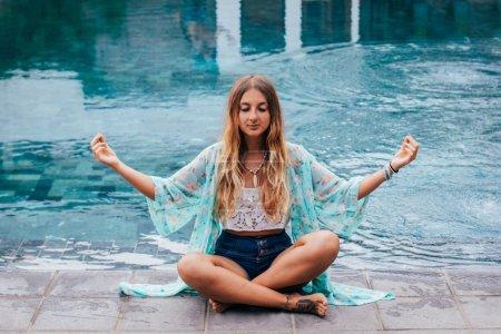 The girl meditates at swimming pool