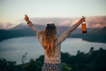 Blond woman holding bottle