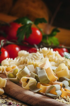 Three-color pasta in the shape of hearts on a wooden table