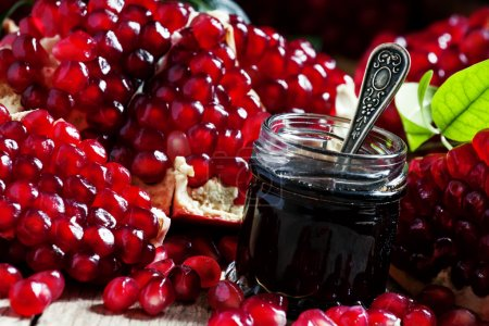 Homemade pomegranate jam in a glass jar with a spo...