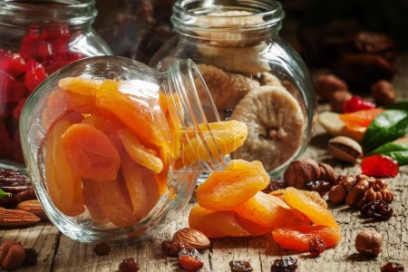 Dried apricots in a glass jar on a dark wooden background
