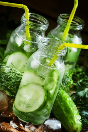 Refreshing cold drink of cucumber and herbs in glass bottles