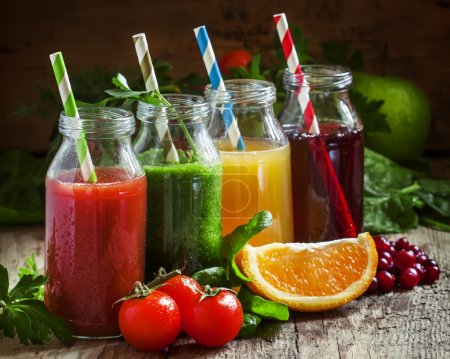 Photo for Bottles with fresh juices from fruits and vegetables on an old wooden background, selective focus - Royalty Free Image