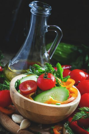 Fresh spring salad with bell pepper, tomato, cucumber, herbs and spices