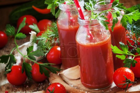 Spicy tomato juice in small bottles with straws