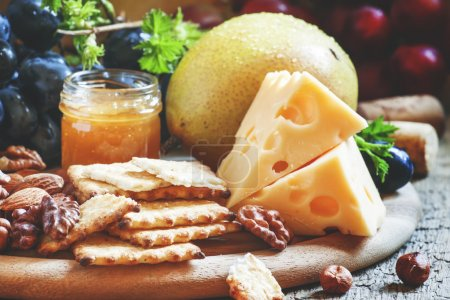 Snack plate: grapes, pears, hazelnuts, almonds, walnuts, cheese Maasdam and honey