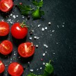 Cut cherry tomatoes on a black background with spices, top view