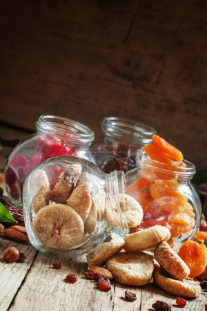 Delicious dried figs in a glass jars on old wooden table