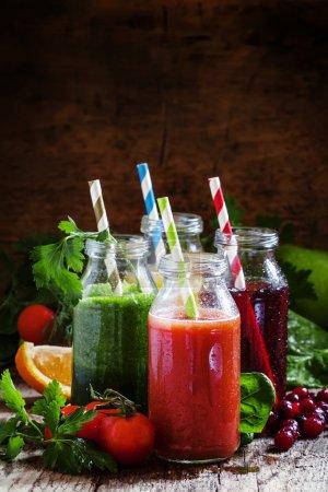 Photo pour Mélange de jus de fruits et légumes sains en petites bouteilles avec des pailles rayées colorées, vieux fond en bois, mise au point sélective - image libre de droit
