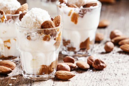 Ice cream with peanut sauce, hazelnuts and almonds in glasses