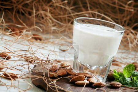 Almonds and milk, old wooden background