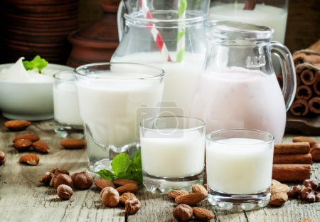 Fresh dairy products and nuts on an old wooden background