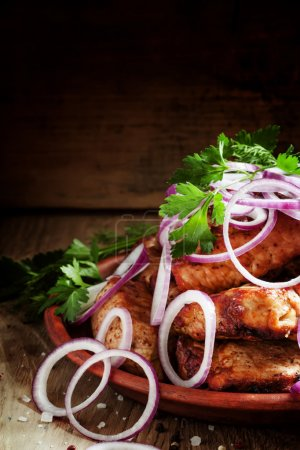 Photo for Traditional Caucasian pork shish kebab with red onion and fresh herbs on a clay dish on the old wooden background, selective focus - Royalty Free Image