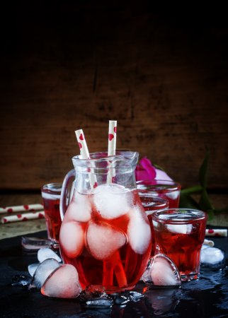 Red drink in a pitcher with ice in the shape of hearts
