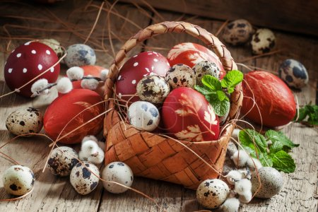Painted eggs and speckled quail eggs in a wicker basket
