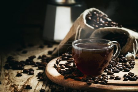 Black coffee in a cup on a background of coffee bags with a coffe maker