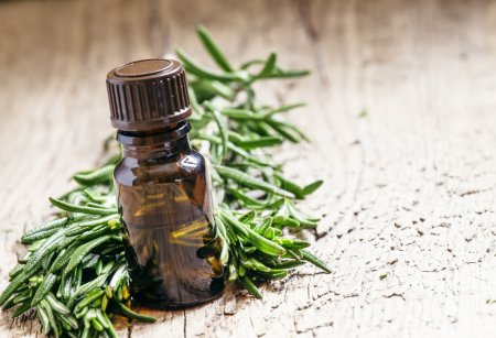 Rosemary essential oil in a small bottle and fresh rosemary