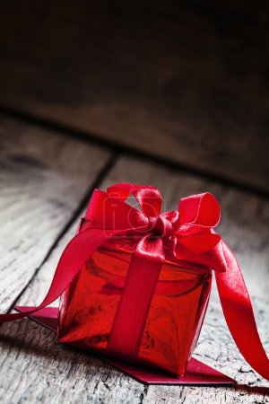 Red gift box tied with a scarlet ribbon with a bow