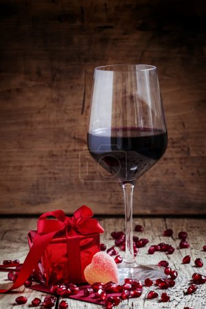Red wine in a glass, a gift in the red packing