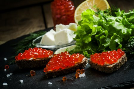 Sandwiches with black rye bread, butter and red salmon caviar