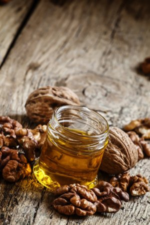 Walnut oil in a small jar and kernels