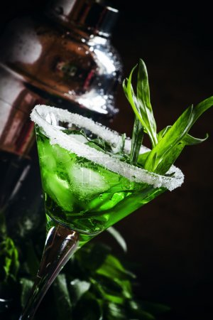 Green cocktail with tarragon and ice in martini glass