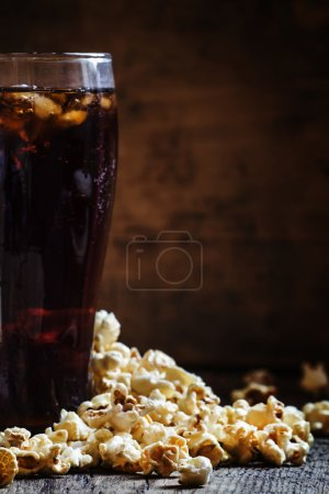 Large glass of cola, salty popcorn spilled on the table