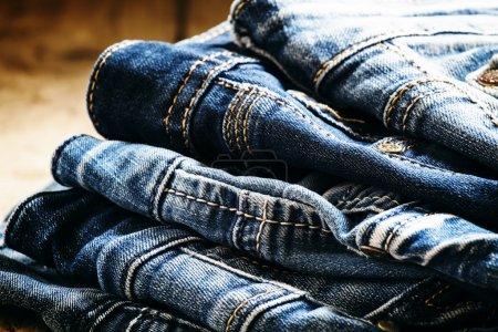 Photo pour Jeans bleus occasionnels classiques, pile sur un fond en bois de cru, foyer sélectif - image libre de droit
