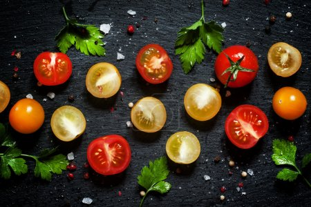 Photo for Food background: red, yellow and orange cherry tomatoes, black background, top view - Royalty Free Image