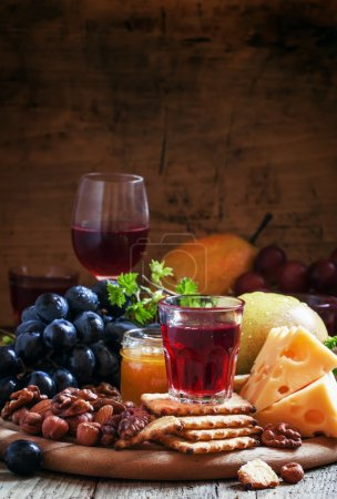 Rose wine and wooden dish with various snacks