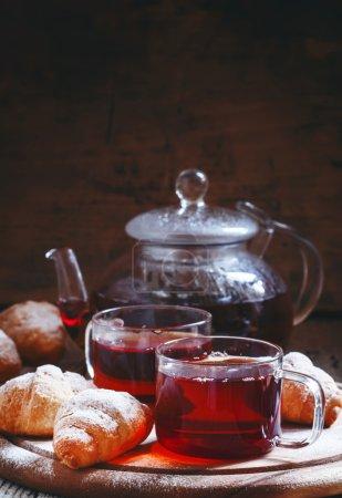 Ceylon black tea in glass cups with kettle, fresh croissants