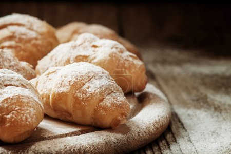 Fresh croissants, sprinkled with powdered sugar