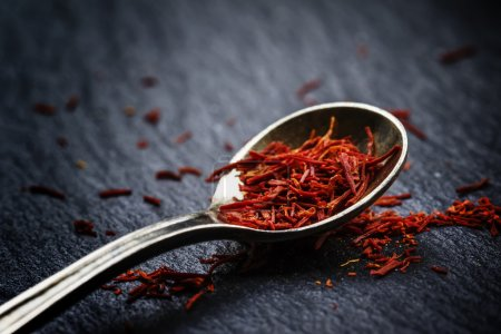 Saffron in a spoon on a dark background