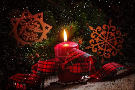 Christmas composition with burning red candle with plaid ribbon