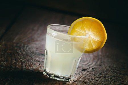 Photo pour Verre unique de vodka avec tranche de citron et de citron sur un vieux fond de bois sombre, image foncée, mise au point sélective - image libre de droit