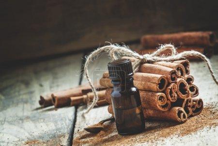 Photo pour Huile essentielle de cannelle dans une petite bouteille, cannelle moulue et bâtonnets de cannelle sur un vieux fond en bois, mise au point sélective - image libre de droit