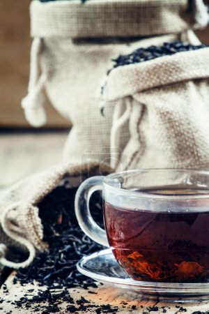 Glass transparent cup of black tea and dry tea in bags