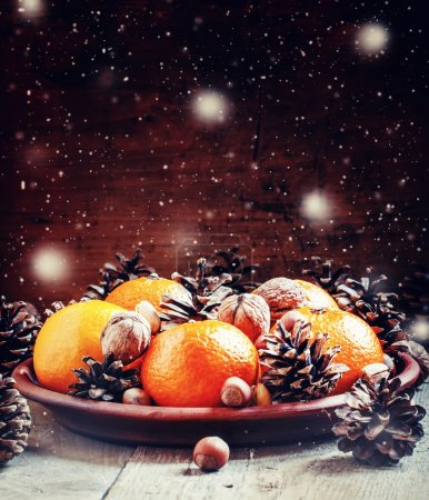 Clay plate with orange mandarins, fir cones, walnuts, hazelnuts and pistachios