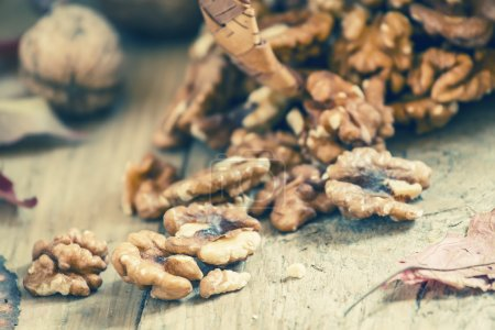 Fresh walnuts spill out of a wicker basket