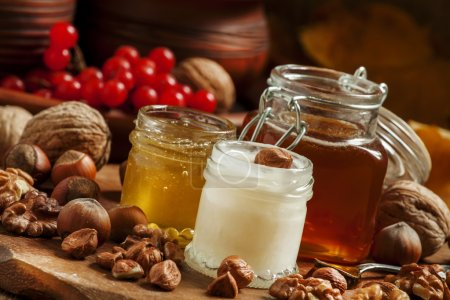 Photo for Three types of honey with walnuts and hazelnuts on the autumn background with fallen leaves in a rustic style, selective focus - Royalty Free Image