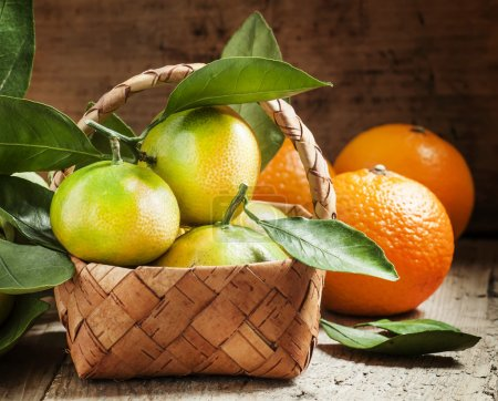 Fresh tangerines with leaves in a wicker basket and oranges