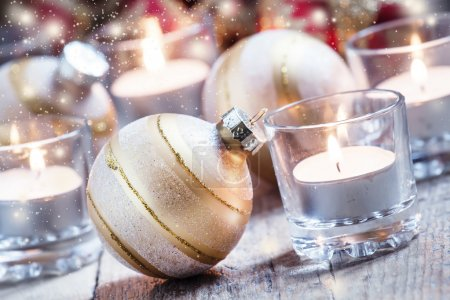 Christmas balls, burning candles on the old wooden background