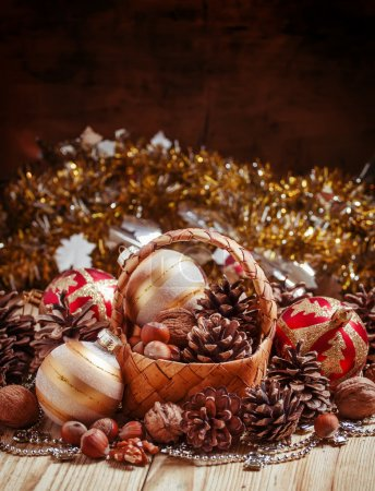 Wicker basket with fir cones, nuts, Christmas balls, tinsel and beads