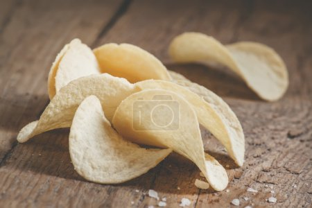 Golden potato chips and sea salt on the old wooden background